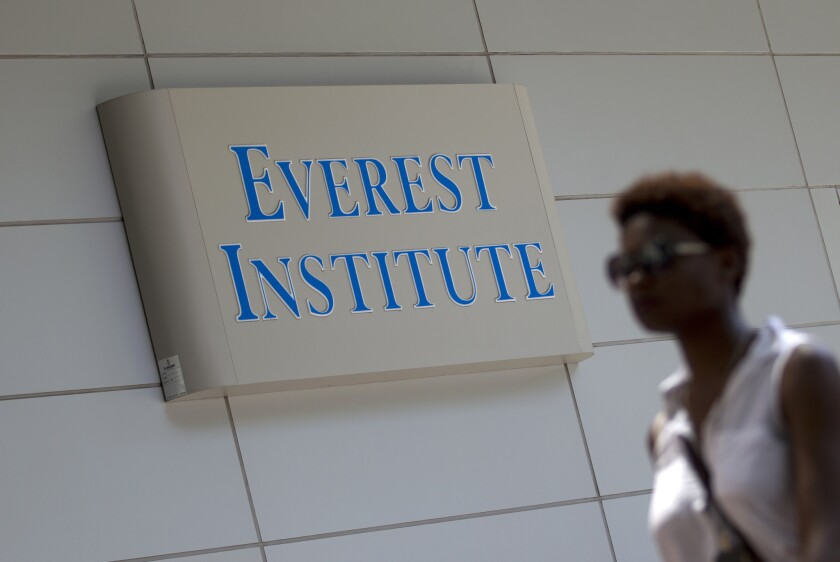 A person walks past an Everest Institute sign in Silver Spring, Md. Corinthian Colleges Inc., which owns Everest, announced Sunday it would cease all operations and shut down more than two dozen remaining schools.