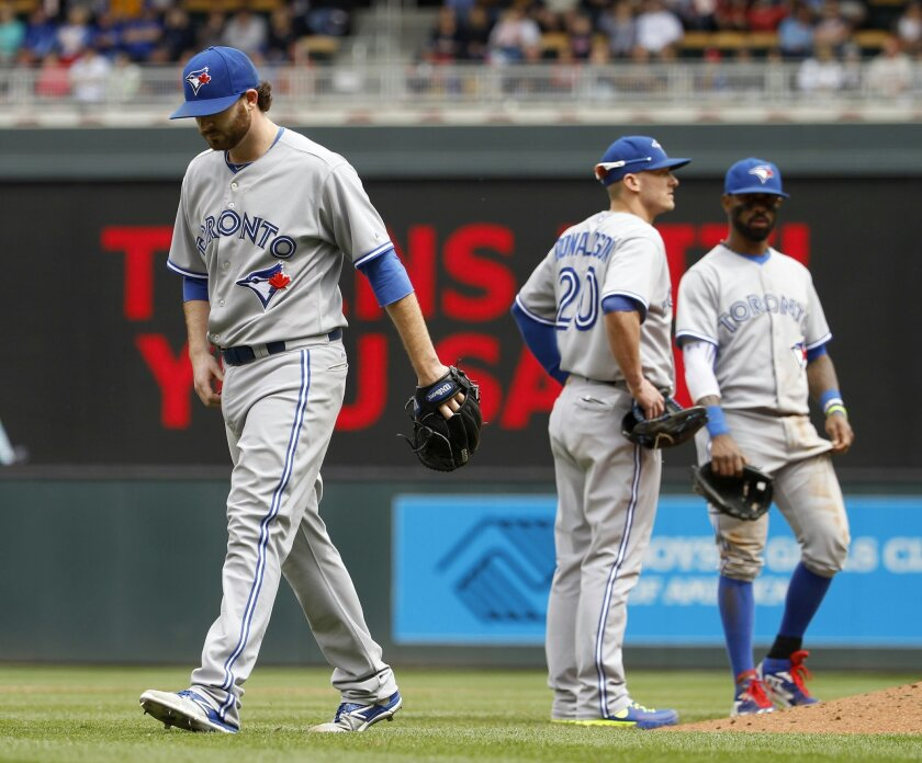 Toronto Blue Jays starting pitcher Drew Hutchison, left, heads to the dugout after being replaced by relief pitcher Roberto Osuna during the sixth inning of a baseball game against the Minnesota Twins in Minneapolis, Sunday, May 31, 2015. The Twins won 6-5. (AP Photo/Ann Heisenfelt)