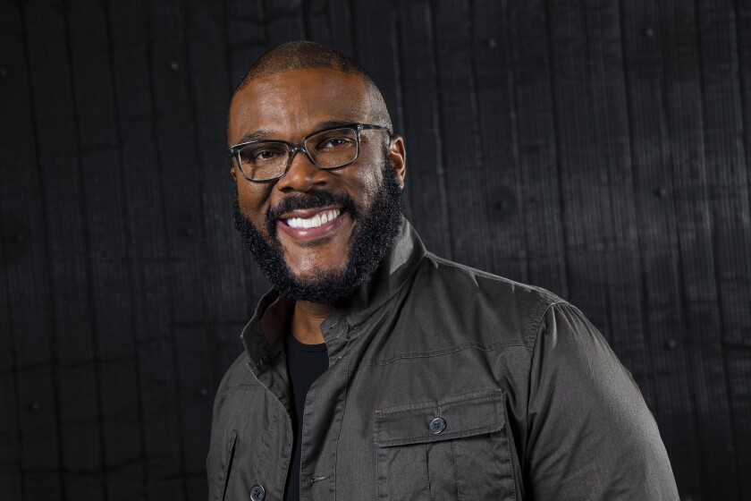 Portrait of Tyler Perry against a charcoal background.