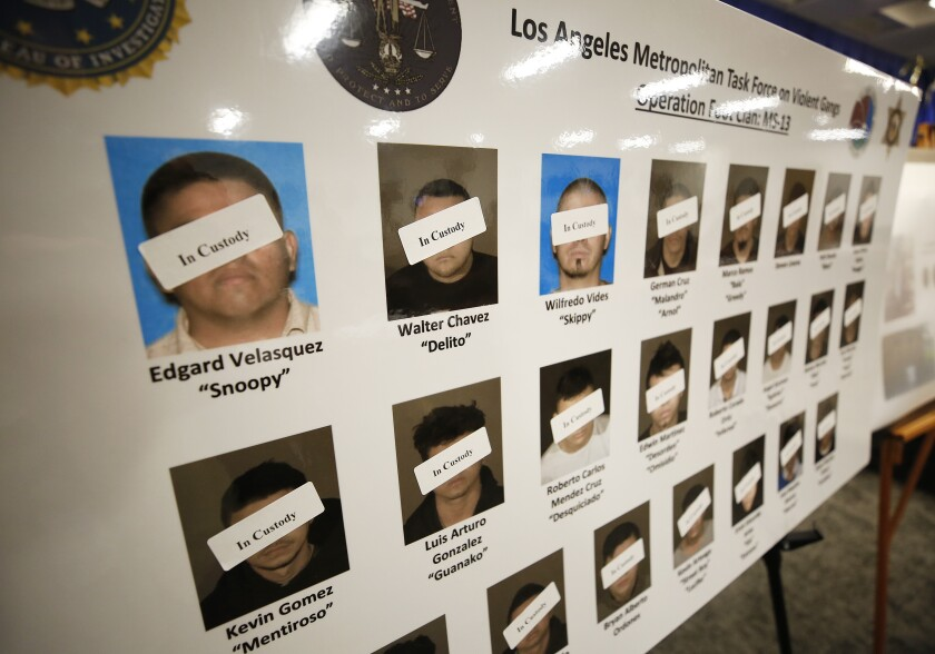 A poster shows defendants in custody as law enforcement officials announce the unsealing of a federal racketeering indictment targeting Los Angeles-based members of the MS-13 gang on July 16.