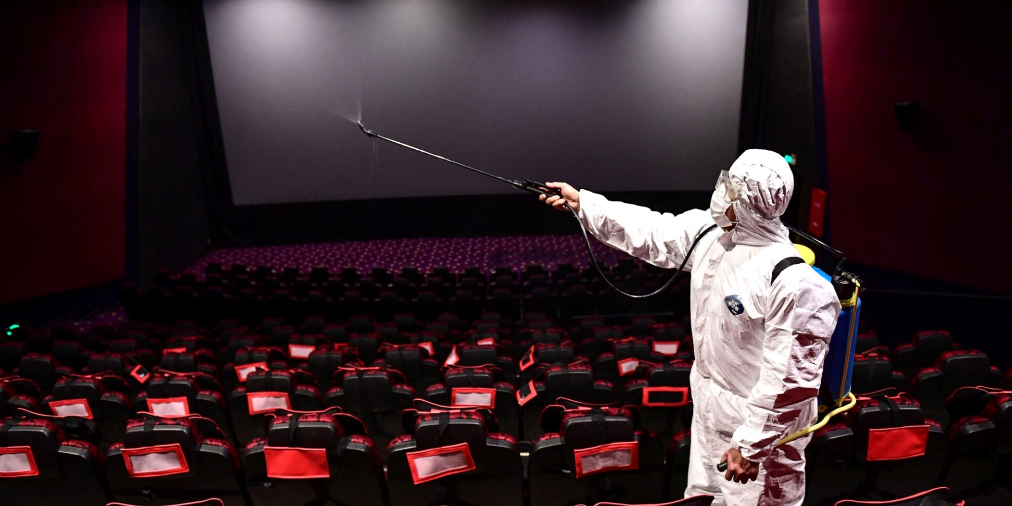 A worker in Shenyang, China, sprays disinfectant at a theater that's expected to reopen.