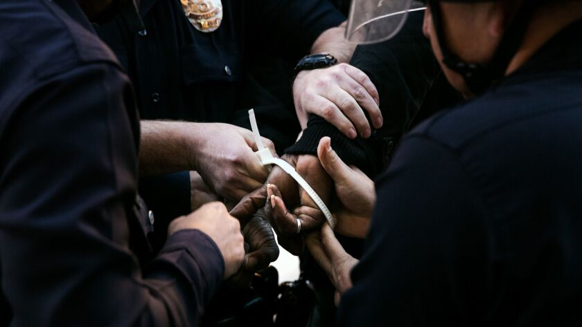 Los Angeles police officers place plastic handcuffs on a protester's hands during a demonstration on Dec. 13, 2014.
