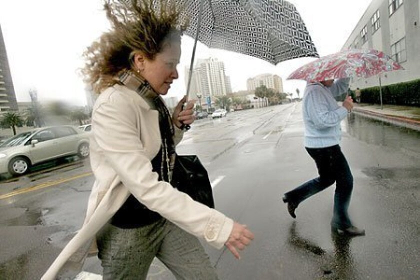 Adrianne Saboya (left) and Susan VanWinkle battled the wind that whipped through downtown San Diego yesterday. (Laura Embry / Union-Tribune)