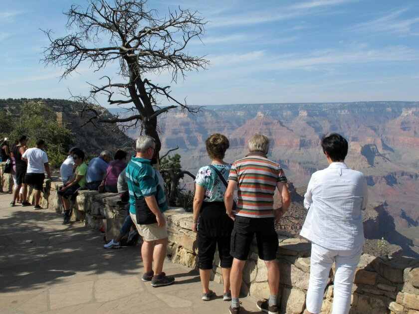 In this Wednesday, Aug. 19, 2015 photo, visitors line the South Rim of Grand Canyon National Park in northern Arizona. The Grand Canyon and other big national parks are seeing more visitors than usual this year, partly driven by good weather, cheap gas and marketing campaigns. (AP Photo/Felicia Fonseca)