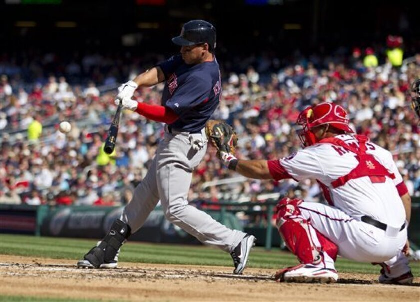 Boston Red Sox' Jacoby Ellsbury hits a single as Washington Nationals catcher Wilson Ramos looks on during the fourth inning of an exhibition baseball game on Tuesday, April 3, 2012 in Washington. (AP Photo/Evan Vucci)