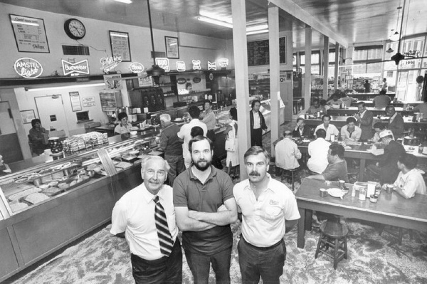 Bill Binder, left, with sons Richard, center, and John inside Philippe's restaurant circa 1982. The sons updated the menu after their father retired but have kept the eatery's hallmarks intact.