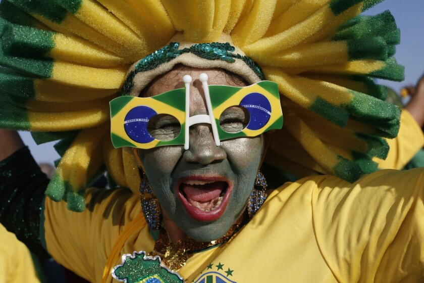 A Brazilian national soccer team fan cheers as she waits for the live broadcast of the World Cup quarterfinals' match between Brazil and Colombia, inside the FIFA Fan Fest area on Copacabana beach, in Rio de Janeiro, Brazil, Friday, July 4, 2014. (AP Photo/Silvia Izquierdo)