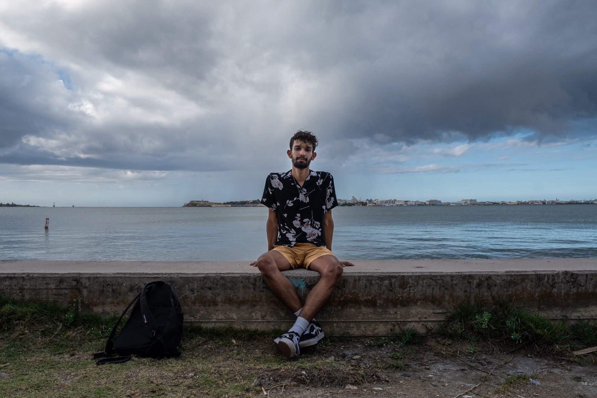 Kemuel Delgado sitting on a short wall, with a beach and the ocean behind him.