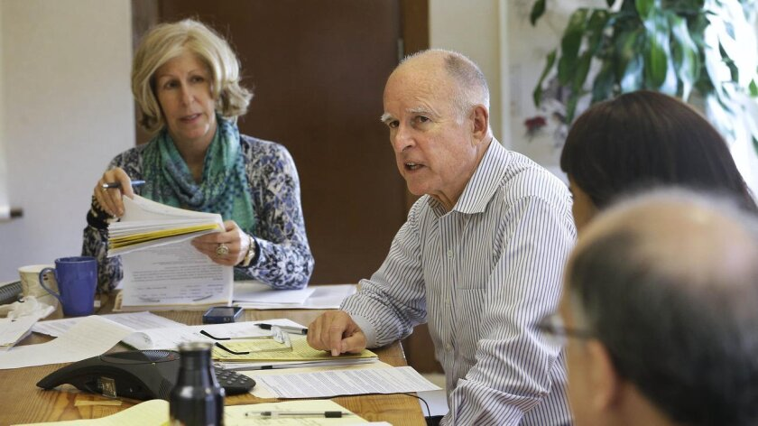 Gov. Jerry Brown discusses a bill with advisers including Executive Secretary Nancy McFadden. [Rich Pedroncelli / Associated Press file]