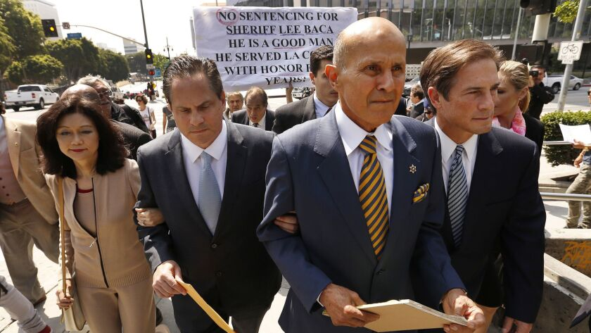 Former L.A. County Sheriff Lee Baca, second from right, leaves federal court last year. Baca was found guilty of obstruction of justice, conspiracy and making false statements in connection with an effort to obstruct an FBI probe into corruption and brutality by jail deputies.