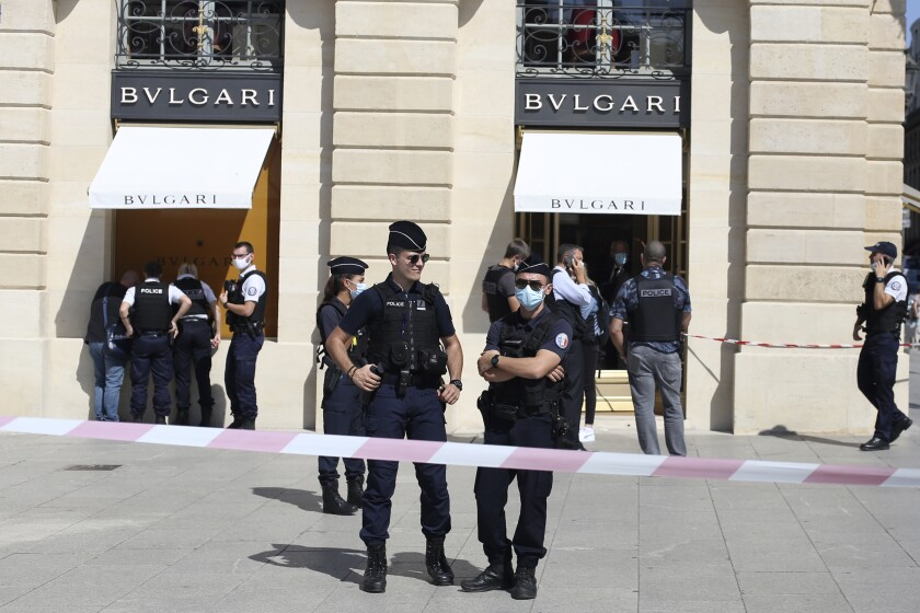 Police officers stand outside the Bulgari jewelry after they arrest two suspects following a Bulgari jewelry heist on the posh Place Vendome in Paris, Tuesday, Sept.7, 2021. One of the suspects was shot in the leg by an officer before being arrested. (AP Photo/Rafael Yaghobzadeh)