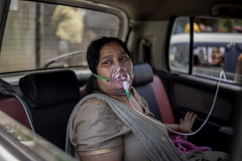 A COVID-19 patient sits inside a car