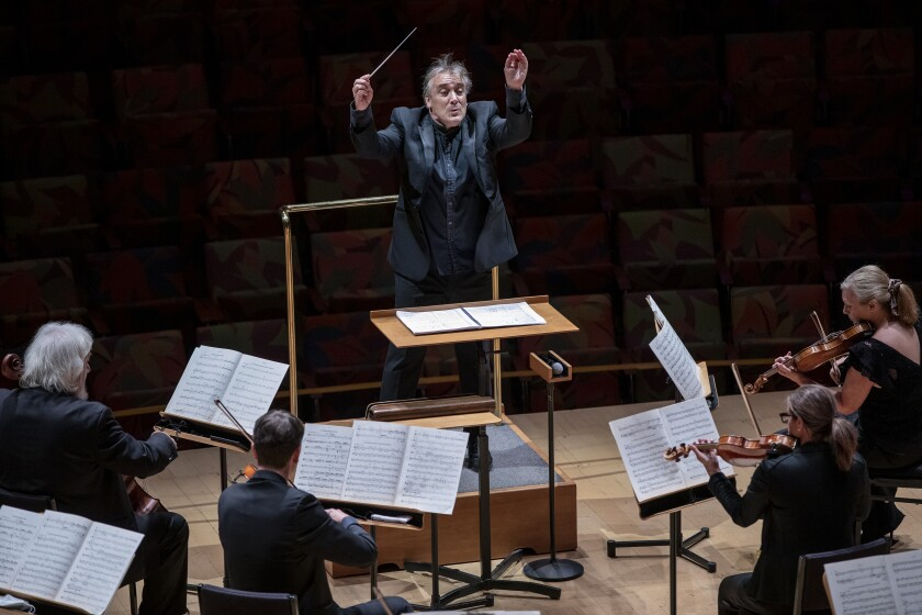 Los Angeles Chamber Orchestra musicians play as conductor Jaime Martín lifts his hands.