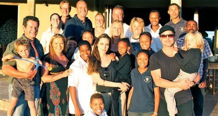 In this photo suplied by Naankuse Wildlife Sanctuary, Brad Pitt, front second from right, and Angelina Jolie, front fifth from right, with their children and owners and staff of the Naankuse Wildlife Sanctuary where Pitt and Jolie spent Christmas with their six children. Jolie and Pitt are donating $2 million to the Nambian sanctuary in the name of their daughter Shiloh, who was born in that country. (AP Photo/Naankuse)