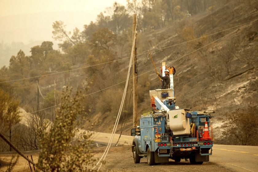 A PG&E worker clears a power line blocking a roadway in unincorporated Napa County on Aug. 20.