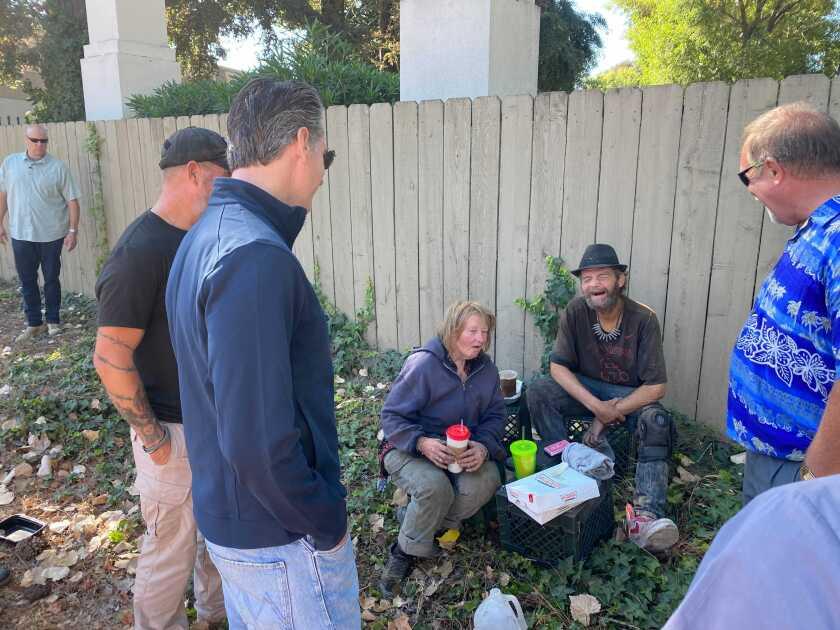 Gov. Gavin Newsom speaks to a couple who are homeless.