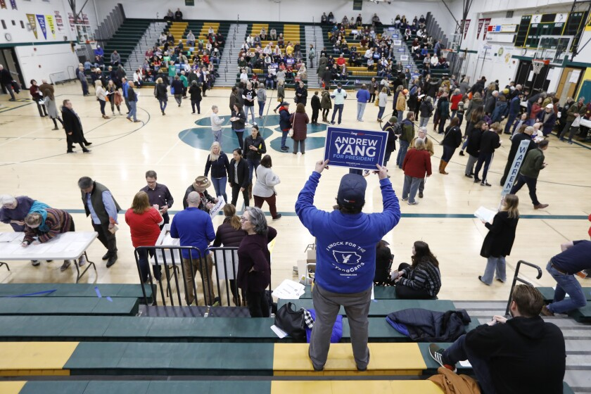 A supporter for Democratic presidential candidate businessman Andrew Yang waits in the stands before a Democratic caucus at Hoover High School, Monday, Feb. 3, 2020, in Des Moines, Iowa. (AP Photo/Charlie Neibergall)