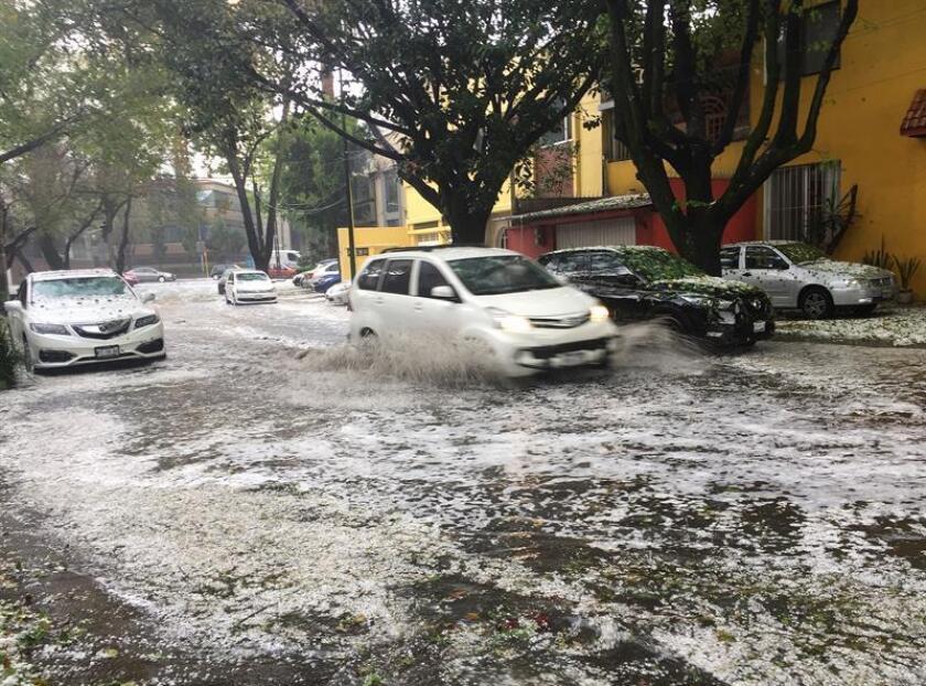 Vista general de una avenida cubierta con granizo hoy, miércoles 14 de marzo de 2018, en Ciudad de México (México). Una intensa lluvia con granizo causó hoy encharcamientos, atascos y demoras en el servicio de transporte, además de dejar un fugaz paisaje navideño en las calles del centro de Ciudad de México. EFE