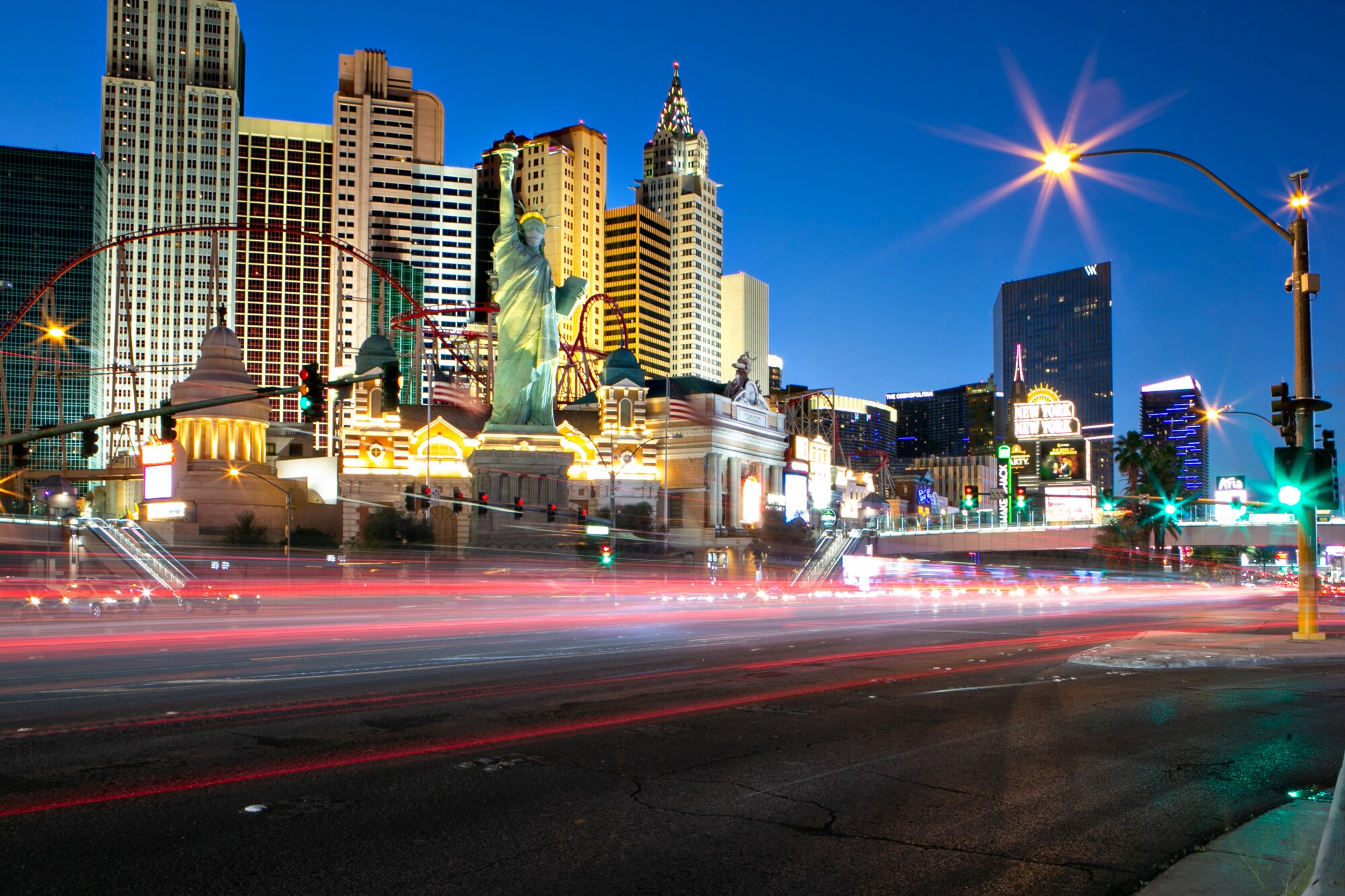 A view of the Las Vegas Strip with blurred headlights from passing cars.