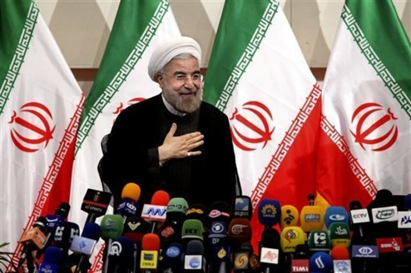 FILE - In this Monday, June 17, 2013 file photo, Iranian President-elect Hasan Rouhani, places his hand on his heart as a sign of respect, after speaking at a news conference, in Tehran, Iran. Rouhani on Monday leveled his first criticism of the outgoing administration since June's election, saying it has mismanaged the country's economy. (AP Photo/Ebrahim Noroozi, File)