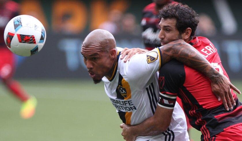 The Galaxy's Nigel de Jong, left, holds off Portland's Diego Valeri on July 23.