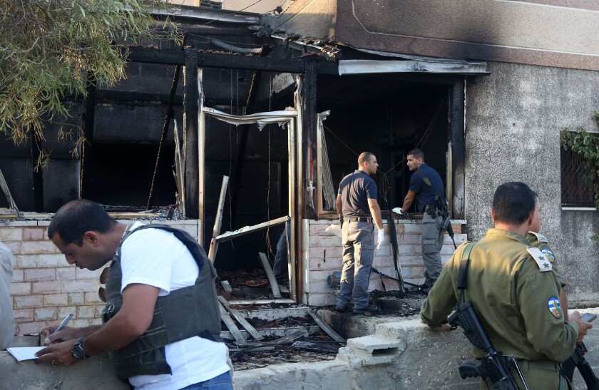 Israeli forces inspect a Palestinian house that was set on fire in the West Bank village of Duma, killing a child, on July 31.