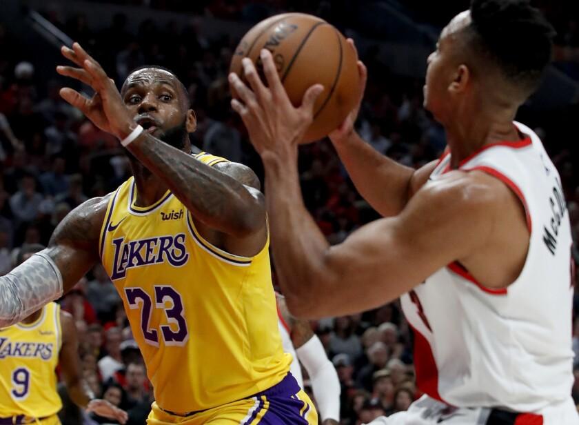 Lakers forward LeBron James defends against Trail Blazers guard CJ McCollum, half of Portland's dynamic backcourt.