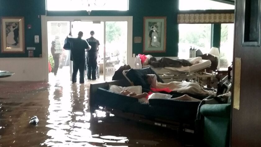 Residents lie on beds surrounded by floodwaters waiting to be evacuated