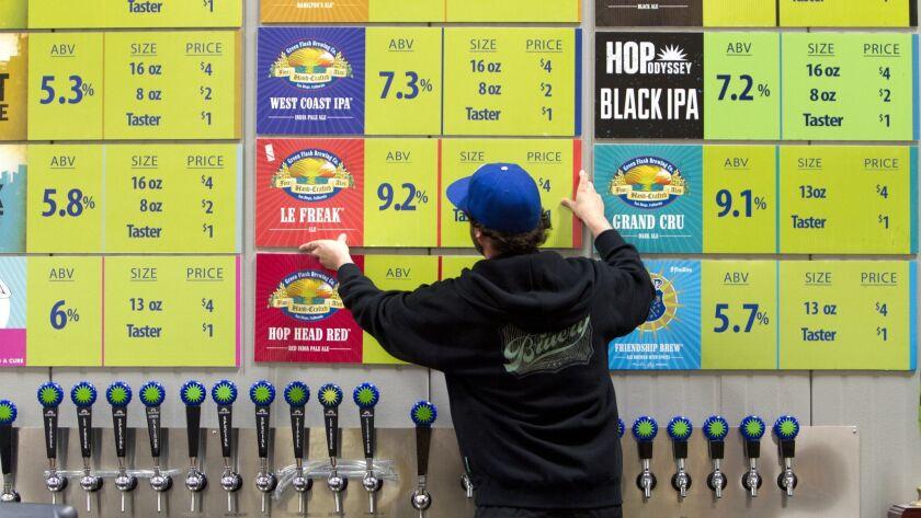 In a 2014 photo, John Silveria adjusts the beer menu at Green Flash's Mira Mesa tasting room.