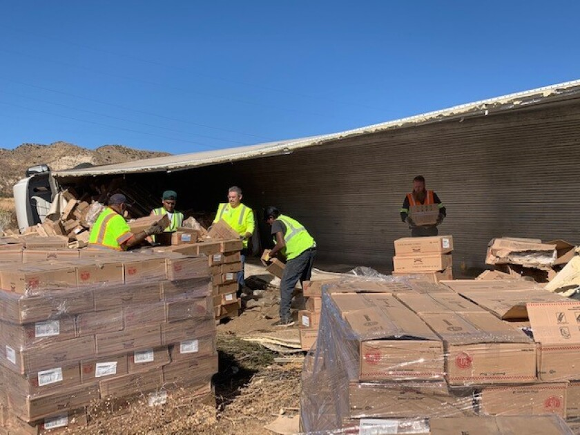 Caltrans crews help clean up hundreds of boxes of cookie dough alongside the Cajon Pass on Thursday.