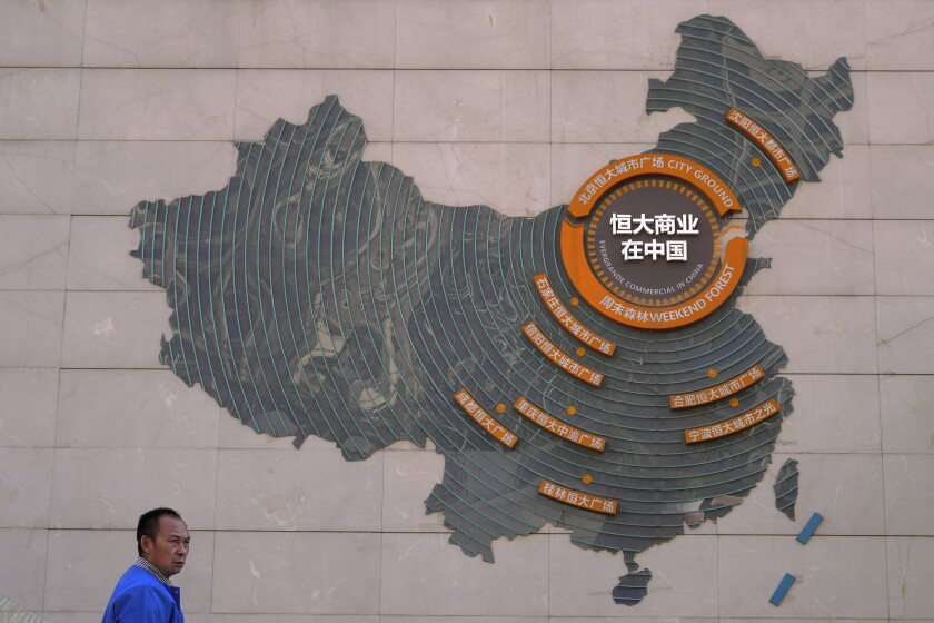 A custodian stands near a map showing Evergrande development projects in China on a wall in an Evergrande city plaza in Beijing, Tuesday, Sept. 21, 2021. Global investors are watching nervously as the Evergrande Group, one of China's biggest real estate developers, struggles to avoid defaulting on tens of billions of dollars of debt, fueling fears of possible wider shock waves for the Chinese financial system. (AP Photo/Andy Wong)