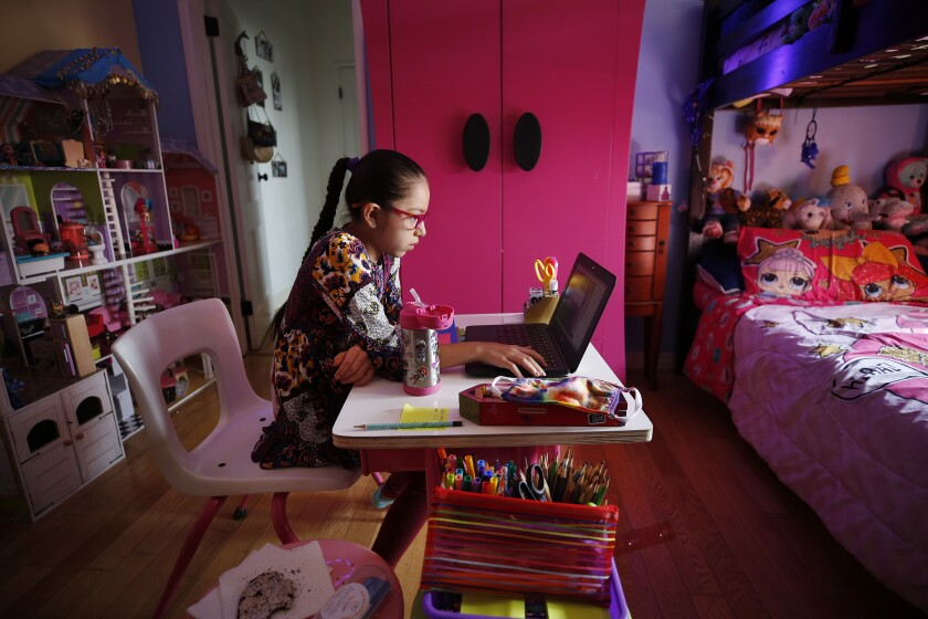 Student participates in an online class in her bedroom during remote learning lessons at home in Boyle Heights.