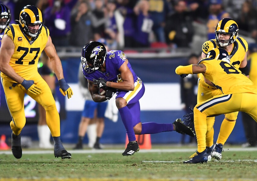 Ravens cornerback Marcus Peters returns an interception against Rams during the fourth quarter of a game Nov. 25 at the Coliseum.