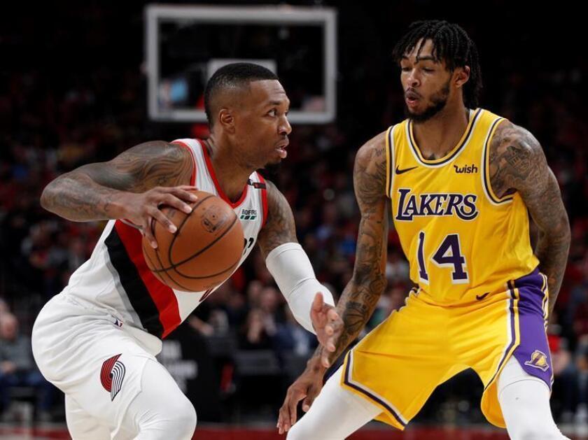 El jugador de los Trail Blazers de Portland Damian Lillard (i) lucha por el balón con Brandon Ingram, de los Lakers de Los Ángeles durante un partido de la NBA. EFE/Archivo