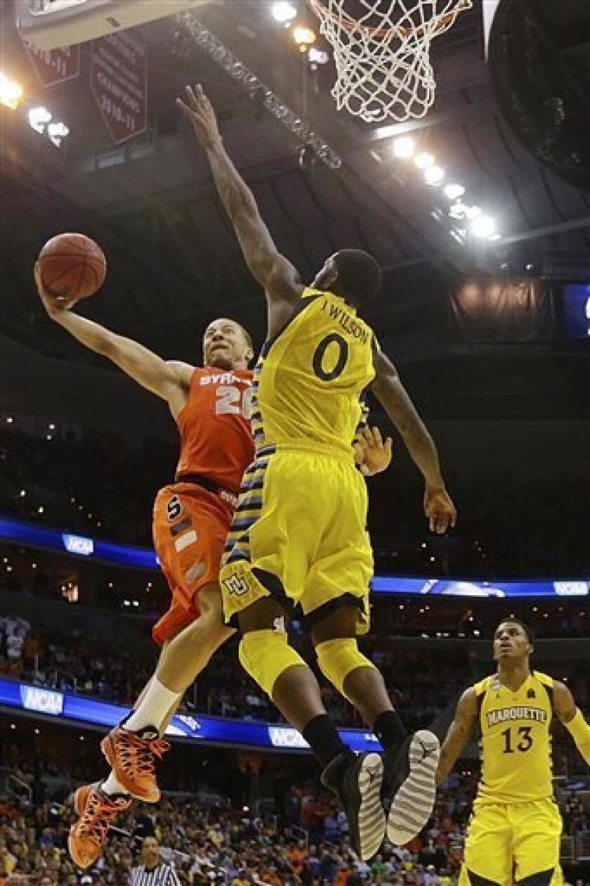 Syracuse guard Brandon Triche (20) shoots as Marquette forward Jamil Wilson (0) defends during the second half of the East Regional final in the NCAA men's college basketball tournament, Saturday, March 30, 2013, in Washington. Syracuse won 55-39. (AP Photo/Pablo Martinez Monsivais)