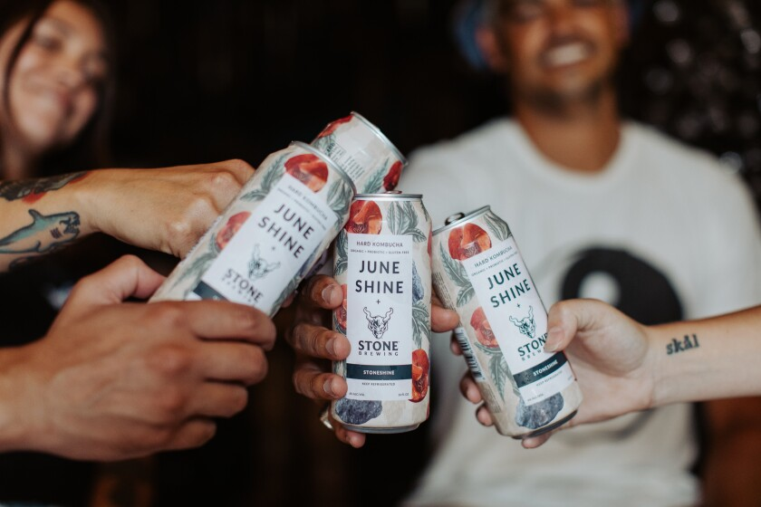 People drinking cans of StoneShine, a new product from JuneShine Hard Kombucha and Stone Brewing