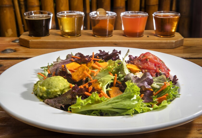 Keep it healthful with  Kekela greens at Big Island Brewhaus in Kamuela, Hawaii.  In the background are Brewhaus draft beer samplers, your pick of five 3.5-ounce glasses, $7.50.
