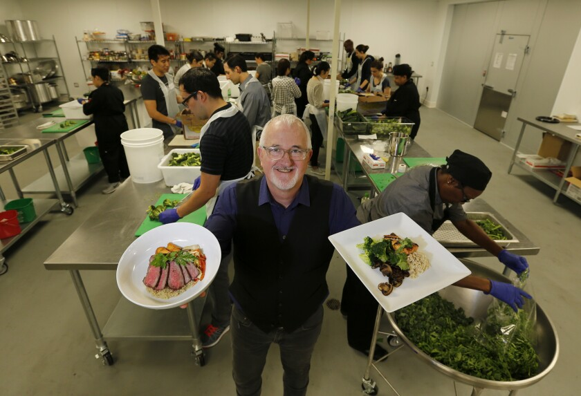 L.A. Kitchen founder Robert Egger holds meals made for the elderly by the workers, students and volunteers behind him. A major aim of the program is to provide job training to former inmates and young adults leaving the foster care system.