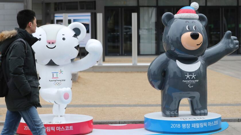 """A man passes by official mascots of the 2018 Pyeongchang Winter Games, a white tiger """"Soohorang"""" for"""