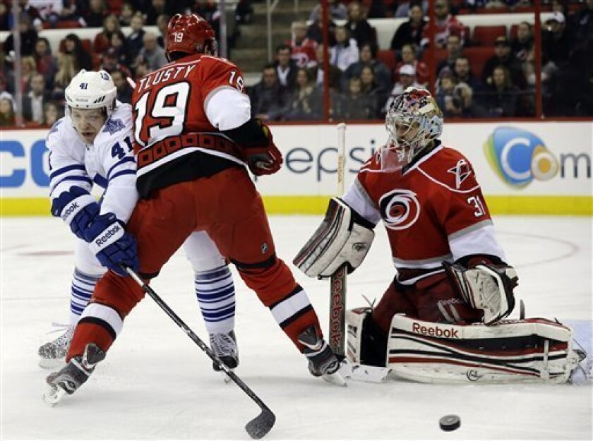 Carolina Hurricanes' Jiri Tlusty (19), of the Czech Republic, and goalie Dan Ellis defend as Toronto Maple Leafs' Nikolai Kulemin (41) tries to score during the first period of an NHL hockey game in Raleigh, N.C., Thursday, Feb. 14, 2013. (AP Photo/Gerry Broome)