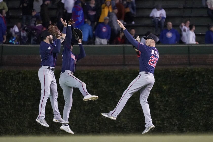 The Minnesota Twins outfielders from left, Jake Cave, Nick Gordon, and Max Kepler celebrate the team's 5-4 win over the Chicago Cubs after a baseball game Wednesday, Sept. 22, 2021, in Chicago. (AP Photo/Charles Rex Arbogast)