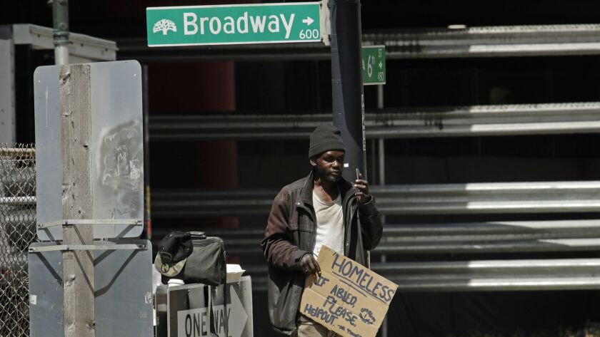 A man waits to panhandle drivers at a traffic signal in Oakland on Friday. California Gov. Gavin Newsom named L.A. County Supervisor Mark Ridley-Thomas as co-chair of a homelessness task force.