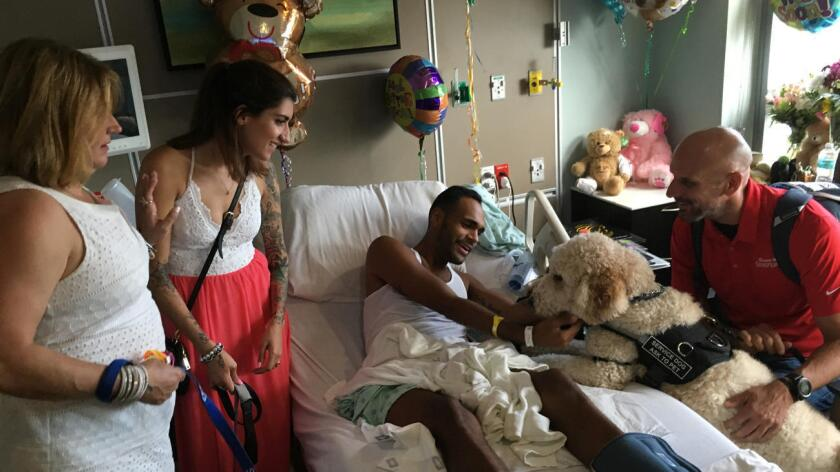 Los sobrevivientes del Maratón de Boston, Sydney Corcoran, Celeste Corcoran (i), y Dave Fortier (d), visitan a Angel Colón, quien fue herido en la discoteca Pulse, en Orlando, Florida.