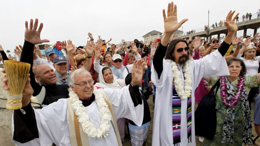 In 2010, the Rev. Christian Mondor, left, offers a prayer to surfers during the Blessing of the Waves ceremony in Huntington Beach.