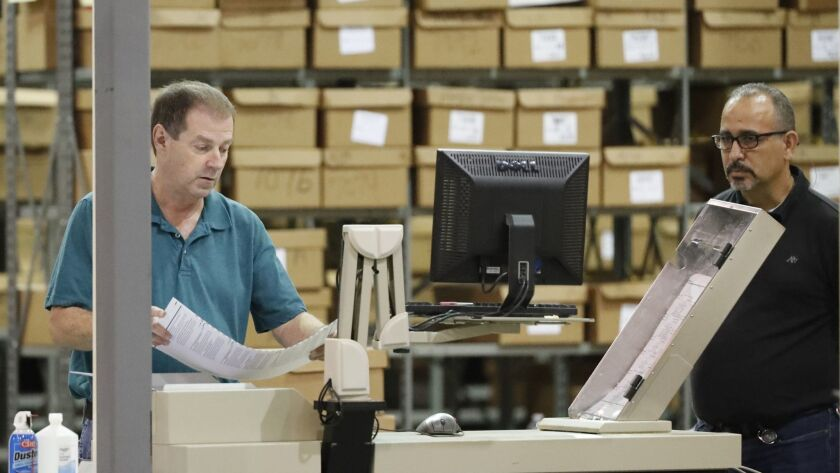 Employees run ballots through a machine before resuming a recount at the Palm Beach County Superviso