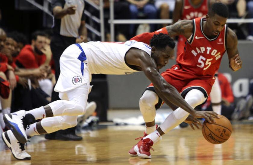 Clippers guard Patrick Beverley dives after a loose ball next to Raptors guard Delon Wright during a preseason game in Honolulu on Oct. 3, 2017.