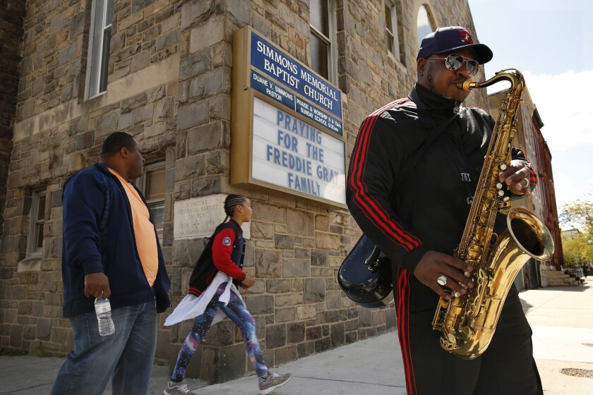 Prestis Vinson plays the saxophone in front of Simmons Memorial Baptist Church in Baltimore, where a sign shows support for Freddie Gray's family.