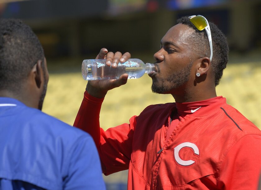 FILE - In this Aug. 15, 2015, file photo, then-Cincinnati Reds relief pitcher Aroldis Chapman, right, takes a drink of water during batting practice as he talks to Los Angeles Dodgers' Yasiel Puig prior to a baseball game, in Los Angeles. New York Yankees closer Aroldis Chapman says he would appeal if he is suspended by Major League Baseball under the sport's new domestic violence policy. Florida prosecutors decided not to file charges against Chapman, whose girlfriend told officers he pushed her, put his hands around her neck and choked her during an argument in October. (AP Photo/Mark J. Terrill, File)
