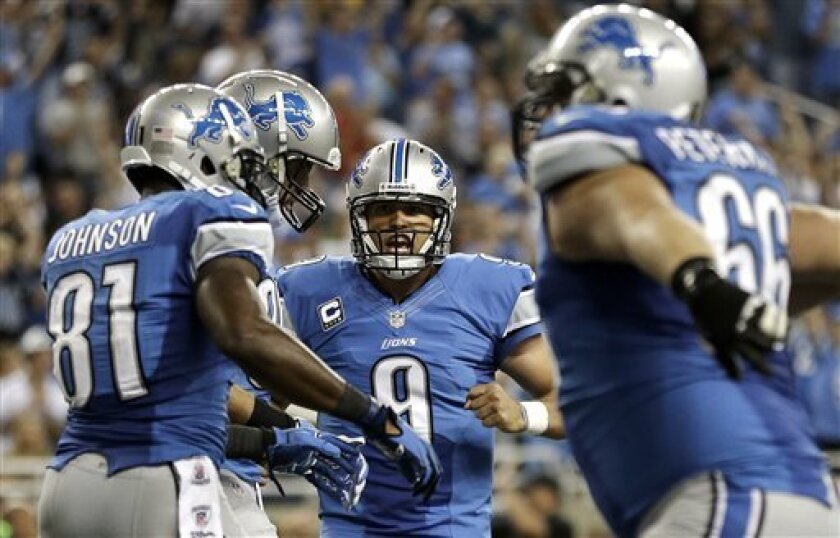 Detroit Lions quarterback Matthew Stafford (9) celebrates his 5-yard touchdow pass to Kevin Smith in the fourth quarter of an NFL football game against the St. Louis Rams in Detroit, Sunday, Sept. 9, 2012. Detroit won 27-23. (AP Photo/Paul Sancya)