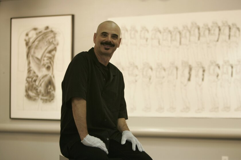 Mark-Elliott Lugo takes a break from installing an exhibit at the Pacific Beach branch library gallery